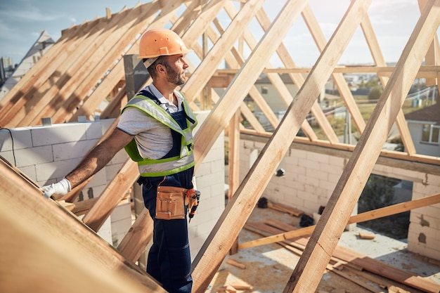 Doordachte bouwer met een gereedschapsriem en een vest met hoge zichtbaarheid die een kijkje neemt op de bouwplaats