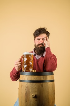 Doordachte brouwer op biervat met bierglas serieuze bebaarde man met ambachtelijk bier man met baard