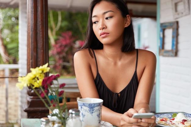 Doordachte brunette aziatische vrouw in casual kleding maakt gebruik van moderne mobiele telefoon voor berichten met vrienden, besteedt vrije tijd in de coffeeshop, geniet van lekker gerecht en warme drank, kijkt peinzend naar beneden.