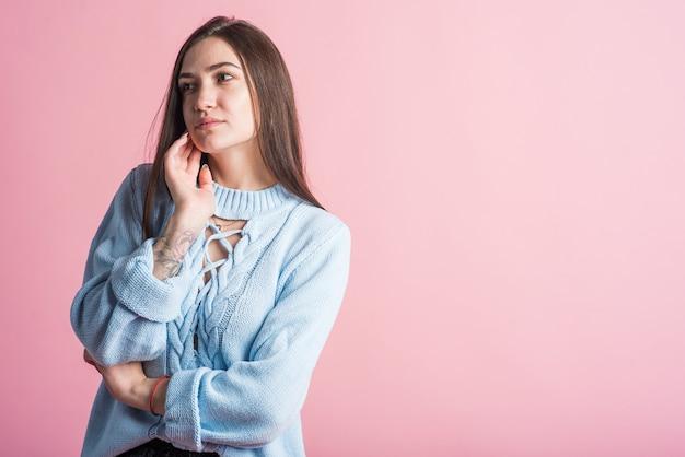 Doordachte brunette meisje in de studio op een roze achtergrond met kopie ruimte