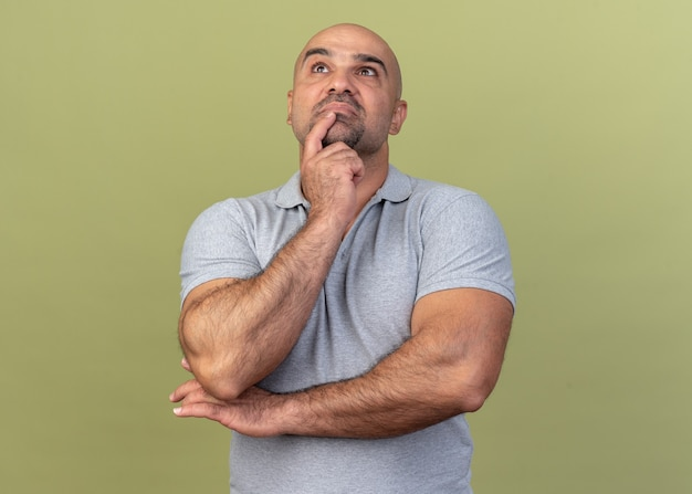 Doordachte casual man van middelbare leeftijd die de vinger op de kin houdt en omhoog kijkt geïsoleerd op olijfgroene muur
