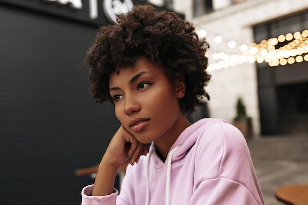 Doordachte charmante krullende vrouw in paarse stijlvolle hoodie leunt, kijkt dromerig weg, poseert buitenshuis