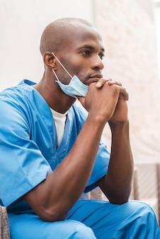 Doordachte chirurg. doordachte jonge afrikaanse arts in blauw uniform leunt met zijn gezicht op handen en kijkt weg terwijl hij op de stoel in de gang zit