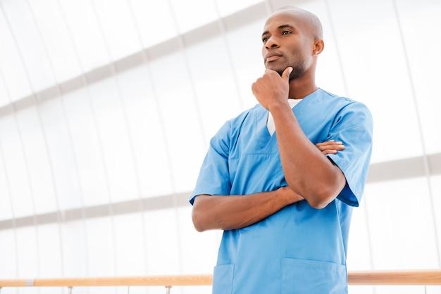 Doordachte chirurg. lage hoekmening van doordachte jonge afrikaanse arts in blauw uniform die de hand op de kin houdt en wegkijkt en de armen gekruist houdt