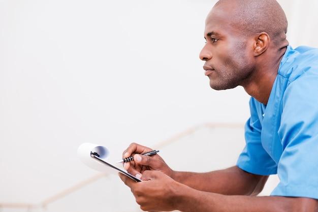 Doordachte chirurg. zijaanzicht van een bedachtzame jonge afrikaanse arts in blauw uniform die iets op het klembord schrijft en wegkijkt terwijl hij tegen de leuning leunt