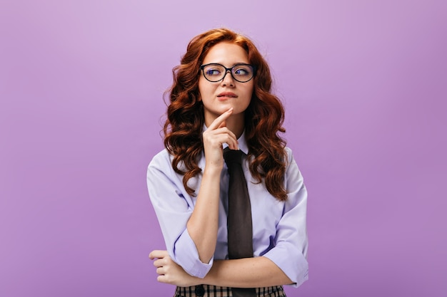 Doordachte dame in shirt en bril poseert op paarse muur