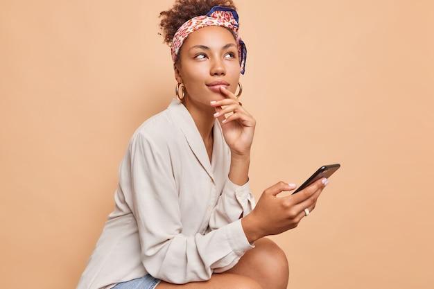 Doordachte dromerige afro-amerikaanse vrouw houdt mobiele telefoon in de hand