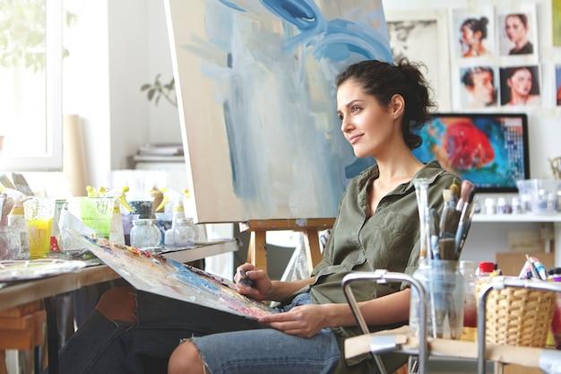 Doordachte dromerige jonge europese vrouwelijke kunstenaar die haar creativiteit tot leven brengt, zittend in haar moderne werkplaatsinterieur met palet en schildersmes. hobby, baan, beroep, kunst en ambacht concept