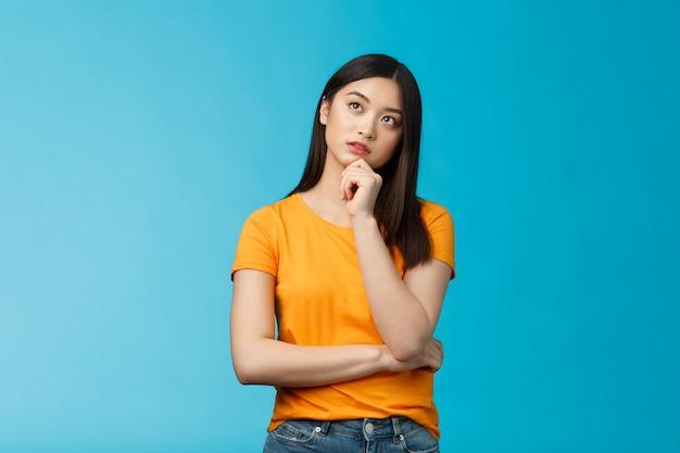Doordachte dromerige slimme aziatische meid die denkt, een plan maakt in het hoofd, de kin aanraakt, gefocust opkijkt, een interessante scène overweegt, nadenkt, een keuze maakt, een beslissing neemt, een blauwe achtergrond neemt.