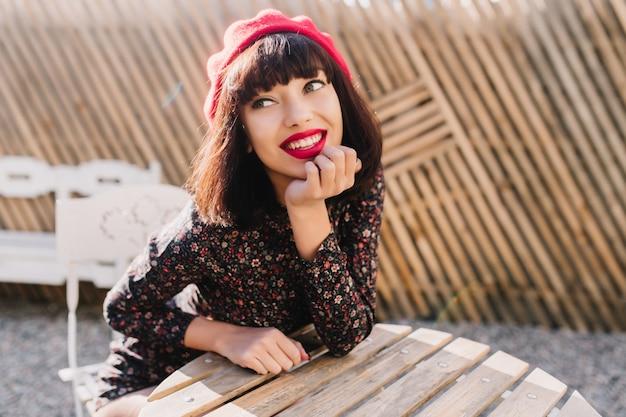 Doordachte elegante frans meisje wacht op koffie in de ochtend, zittend aan de houten tafel in een straatcafé. portret van dromerige jonge vrouw met kort kapsel trendy rode baret en vintage jurk dragen