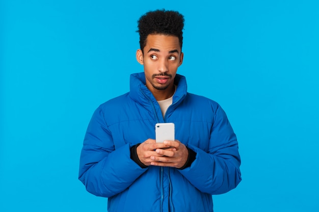 Doordachte en creatieve schattige afro-amerikaanse man denken, gebruik de verbeelding om een schattig bericht te schrijven vriendin, uitnodigend kom datum valentijnsdag, met smartphone nadenkend, blauwe achtergrond