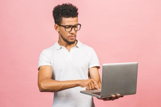 Doordachte ernstige afro-amerikaanse man met laptop