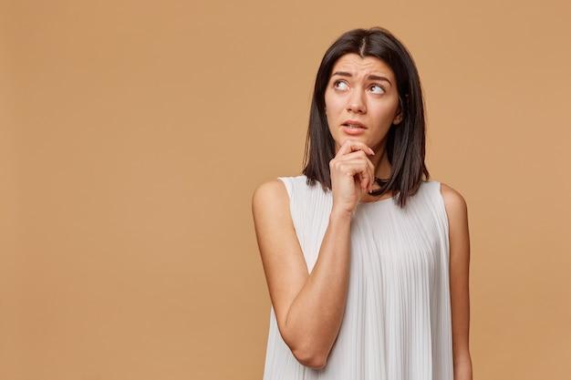 Doordachte gebruinde vrouw staande hand met kin kijkend naar de linkerbovenhoek naar de lege copyspace met een beetje voorzichtigheid, beeldt de opwinding af,