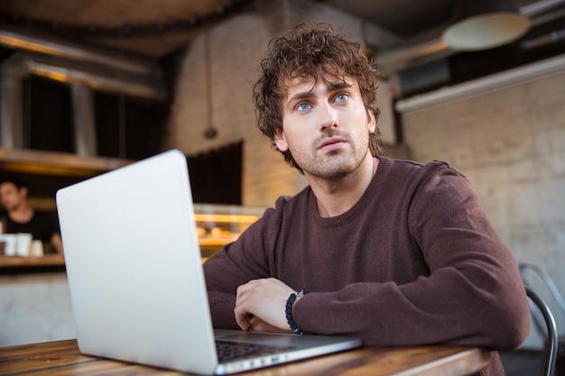 Doordachte gekrulde peinzende geconcentreerde knappe jongeman in bruin sweetshirt die met laptop in café werkt