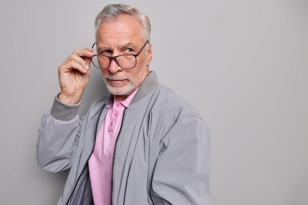 Doordachte, gerimpelde grijsharige man denkt na over iets serieus
