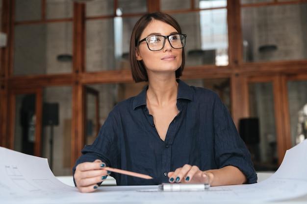 Doordachte glimlachende zakenvrouw in brillen zitten bij de tafel