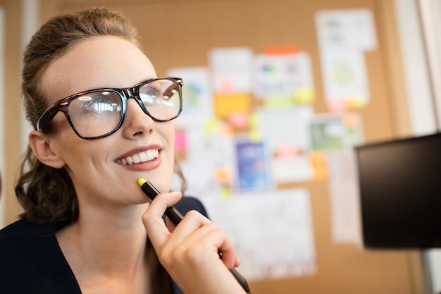 Doordachte glimlachende zakenvrouw wegkijken in kantoor