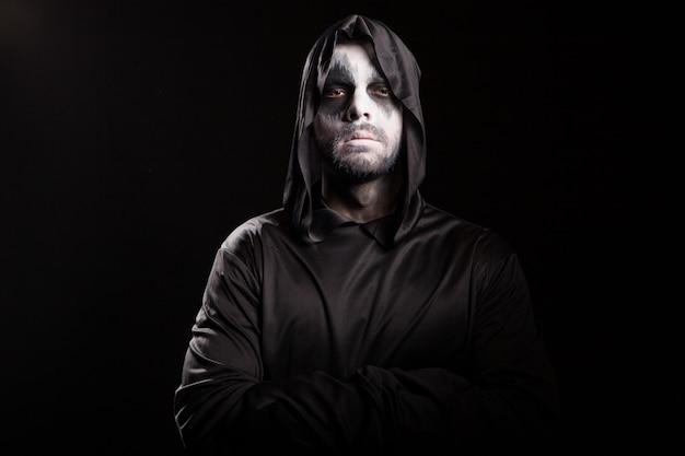 Doordachte grim reaper op zwarte achtergrond. spookachtig monster.