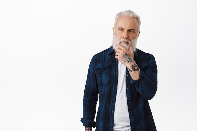 Doordachte hipster oude man raakt zijn baard aan en kijkt naar de linkerbovenhoek, overweegt een keuze, denkt aan iets serieus, staat over een witte muur