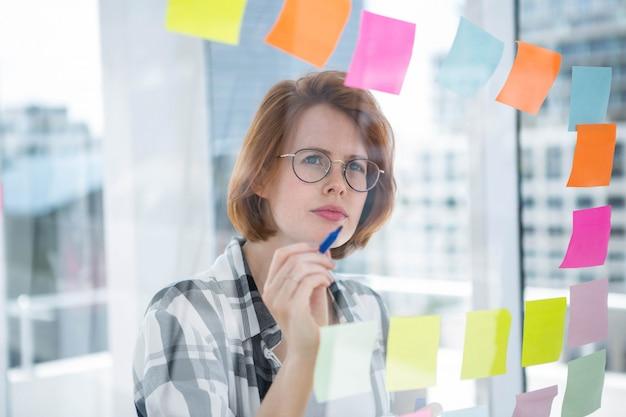 Doordachte hipster vrouw, staande in haar kantoor, het lezen van notities over het geheel