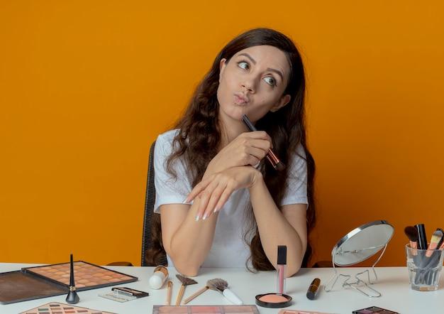 Doordachte jong mooi meisje zit aan de make-up tafel met make-up tools blozen borstel te houden en kin aan te raken met het kijken naar kant geïsoleerd op een oranje achtergrond
