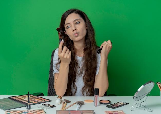 Doordachte jong mooi meisje zit aan de tafel van de make-up met make-up tools houden blozen en poeder borstels kijken naar een van hen geïsoleerd op groene achtergrond