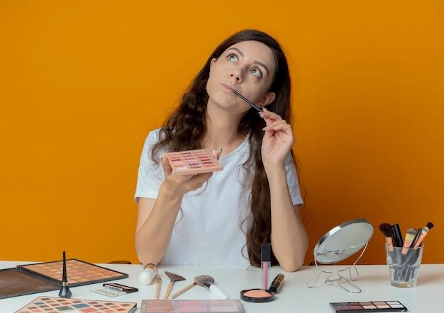 Doordachte jong mooi meisje zit aan de tafel van de make-up met make-up tools opzoeken oogschaduw palet houden en aanraken van lippen met oogschaduw borstel geïsoleerd op een oranje achtergrond