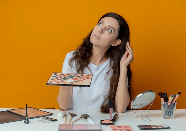 Doordachte jong mooi meisje zit aan de tafel van de make-up met make-up tools opzoeken oogschaduw palet te houden en hoofd met oogschaduw borstel geïsoleerd op een oranje achtergrond aan te raken