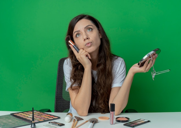 Doordachte jong mooi meisje zit aan de tafel van de make-up met make-up tools spiegel te houden en het aanraken van gezicht met blozen borstel opzoeken geïsoleerd op groene achtergrond