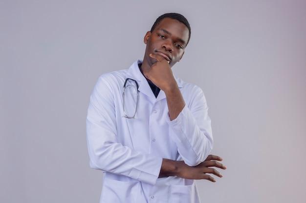 Doordachte jonge afro-amerikaanse mannelijke arts, gekleed in witte jas met een stethoscoop met hand op kin met peinzende uitdrukking