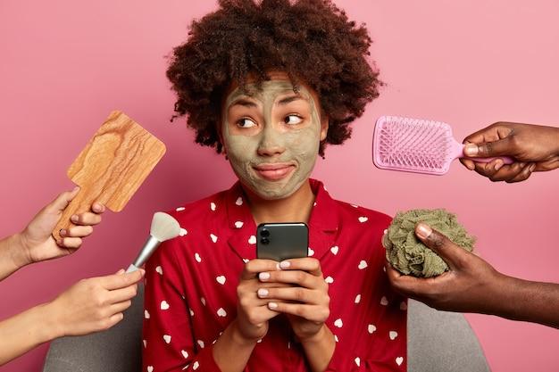 Doordachte jonge afro-amerikaanse vrouw kijkt bedachtzaam opzij, zoekt internet op mobiele telefoon tijdens schoonheidsbehandelingen, heeft kleimasker op gezicht aangebracht