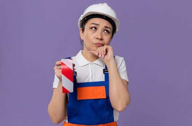 Doordachte jonge aziatische bouwvrouw met een witte veiligheidshelm die waarschuwingstape vasthoudt en naar de zijkant kijkt