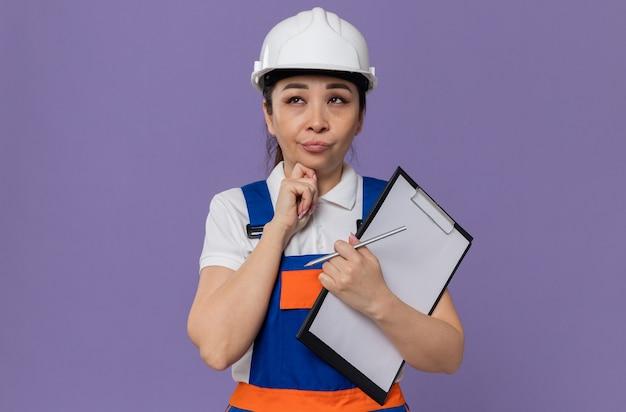Doordachte jonge aziatische bouwvrouw met witte veiligheidshelm die klembord vasthoudt en omhoog kijkt