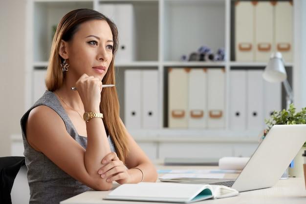 Doordachte jonge aziatische zakenvrouw met rood haar die met pen aan tafel zit en alleen aan een project werkt