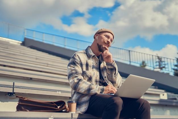 Doordachte jonge, bebaarde man met snor werkt buiten terwijl hij de laptop op de benen in de stad houdt