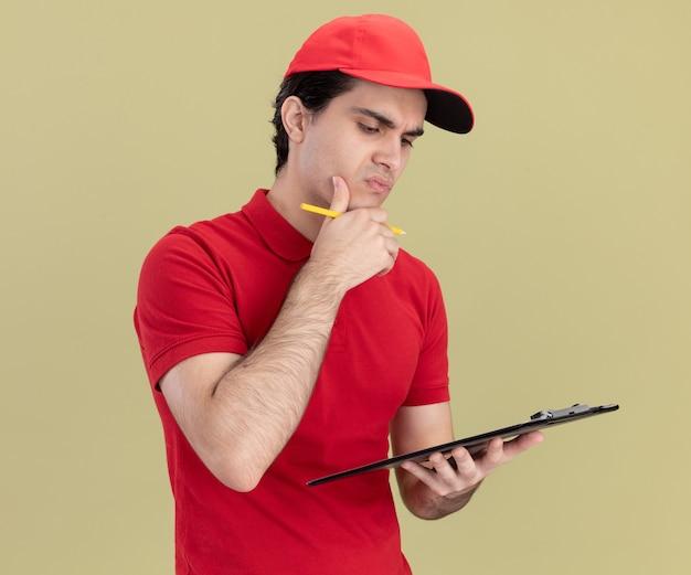 Doordachte jonge bezorger in rood uniform en pet met klembord en potlood kijken naar klembord aanraken kin geïsoleerd op olijfgroene muur