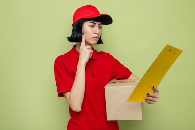Doordachte jonge blanke bezorger die kartonnen doos vasthoudt en naar klembord kijkt
