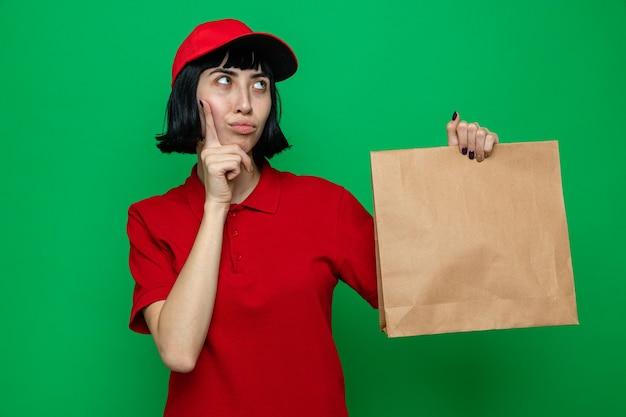 Doordachte jonge blanke bezorger die voedselverpakking vasthoudt en omhoog kijkt