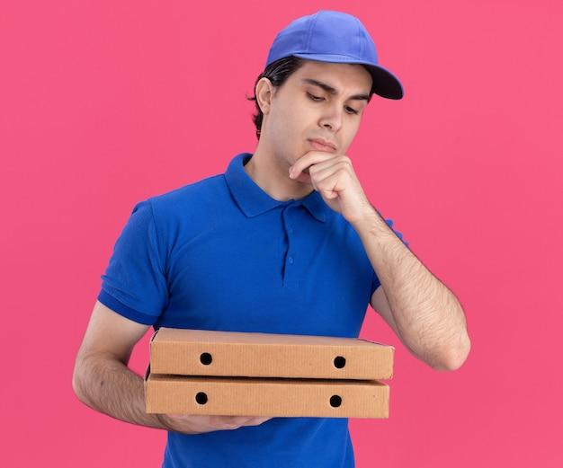 Doordachte jonge blanke bezorger in blauw uniform en pet die pizzapakketten vasthoudt en bekijkt, hand op kin geïsoleerd op roze muur