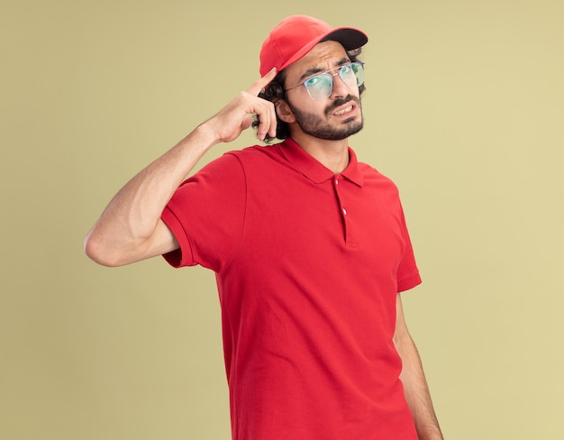 Doordachte jonge blanke bezorger in rood uniform en pet met een bril die een denkgebaar doet geïsoleerd op een olijfgroene muur