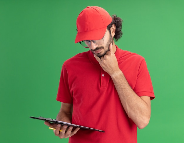 Doordachte jonge blanke bezorger in rood uniform en pet met een bril met klembord en potlood die de hand op de kin houdt en naar klembord kijkt