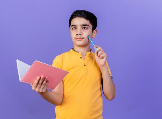 Doordachte jonge blanke jongen met notitieblok wang aanraken met potlood kijken kant geïsoleerd op paarse muur met kopie ruimte