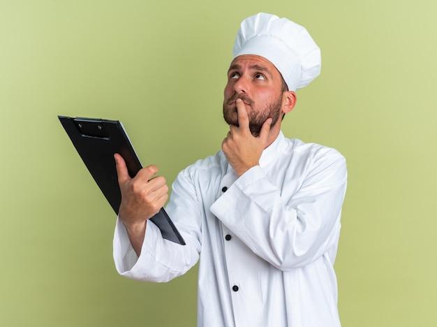 Doordachte jonge blanke mannelijke kok in chef-kok uniform en pet met klembord aanraken lip met vinger omhoog kijkend