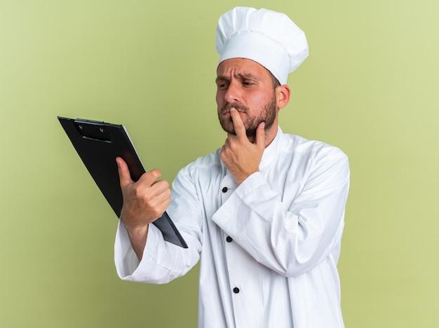 Doordachte jonge blanke mannelijke kok in chef-kokuniform en pet die vasthoudt en naar klembord kijkt en lip met vinger aanraakt