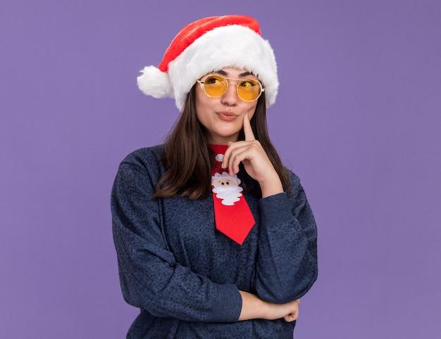 Doordachte jonge blanke meisje in zonnebril met kerstmuts en santa stropdas legt vinger op gezicht en kijkt naar kant geïsoleerd op paarse muur met kopie ruimte