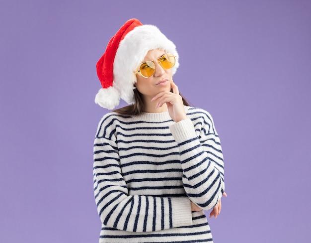 Doordachte jonge blanke meisje in zonnebril met kerstmuts legt hand op de kin en kijkt naar de zijkant