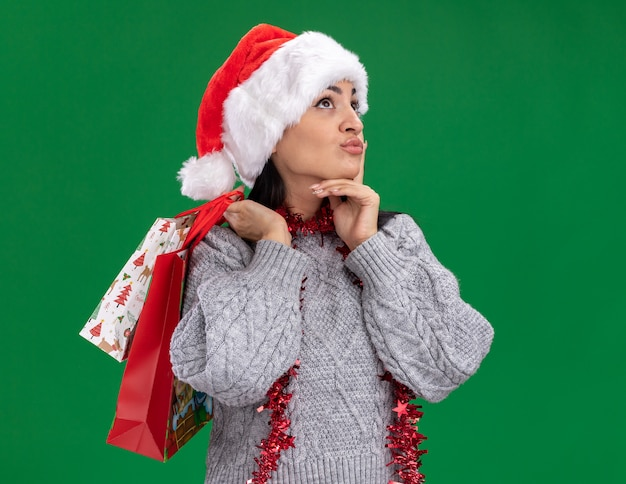 Doordachte jonge blanke meisje met kerstmuts en klatergoud slinger rond de nek houden kerstcadeauzakken op schouder opzoeken houden hand op kin geïsoleerd op groene achtergrond