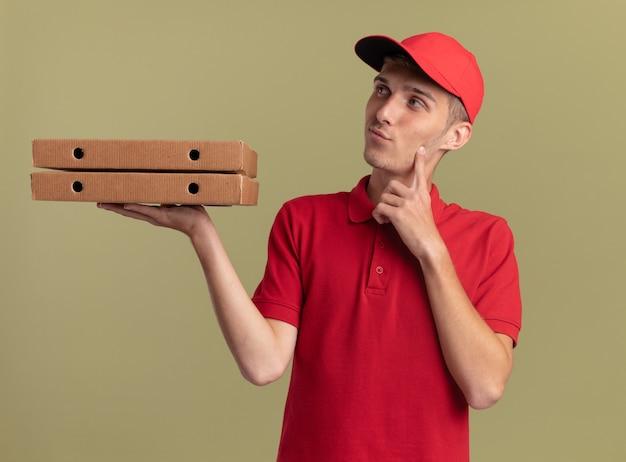 Doordachte jonge blonde bezorger legt vinger op kin terwijl hij pizzadozen vasthoudt en kijkt naar kant geïsoleerd op olijfgroene muur met kopieerruimte