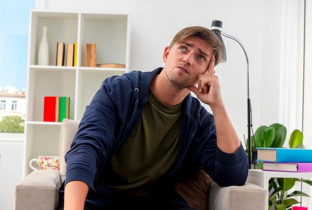 Doordachte jonge blonde knappe man zit op fauteuil vinger zetten tempel opzoeken in woonkamer