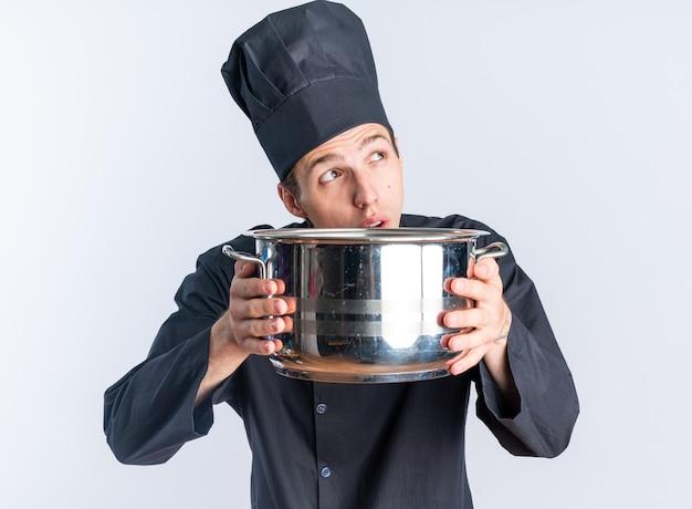 Doordachte jonge blonde mannelijke kok in chef-kok uniform en pet met pot omhoog kijkend